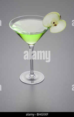 Apple Martini mixed drink with apple slice garnish on grey background - Stock Photo