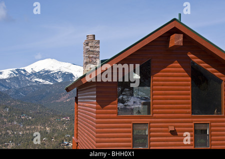 Underneath the blue sky, a log cabin has a beautiful view of snowcapped Sierra Blanca and Ruidoso valley - Ruidoso, - Stock Photo