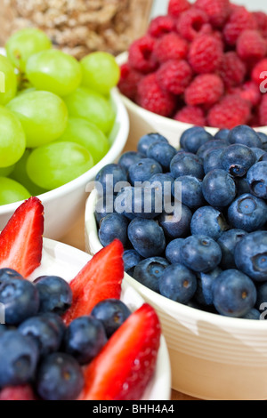 Bowls of healthy breakfast strawberries and blueberries in yogurt with raspberries, blueberries grapes and granola - Stock Photo