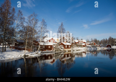 A village by a small river in the winter, Sweden. - Stock Photo