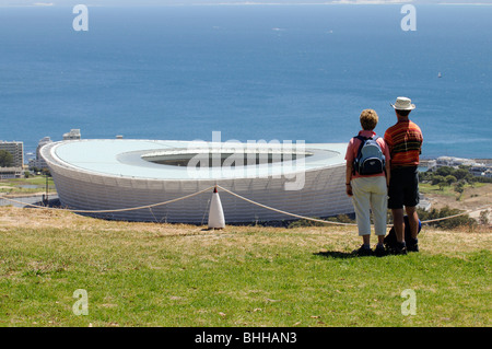 Tourists overlook the Green Point Stadium in Cape Town built for the World Cup 2010 seen from Signal Hill - Stock Photo