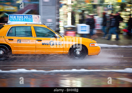 Yellow Taxi in the winter in Times Square, New York City - Stock Photo