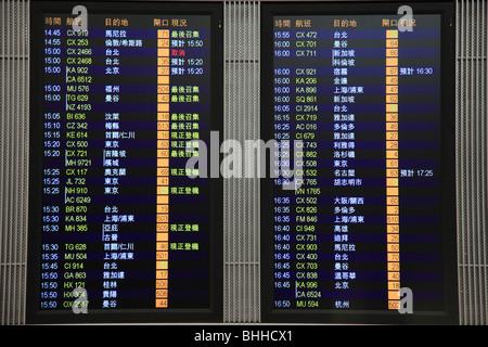 China, Hong Kong, Chek Lap Kok Airport, departures screen in Chinese - Stock Photo