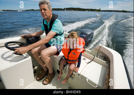 Grandfather and grandson in a boat, Stockholm archipelago, Sweden. - Stock Photo