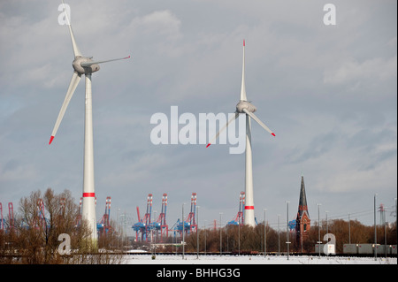 GERMANY Hamburg, Enercon windmill E-126 with 6 MW in Altenwerder during winter, CTA Container terminal and church - Stock Photo
