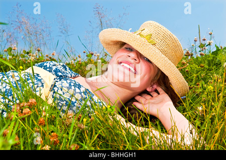 Young teenage girl laying on summer meadow amid wildflowers in straw hat - Stock Photo