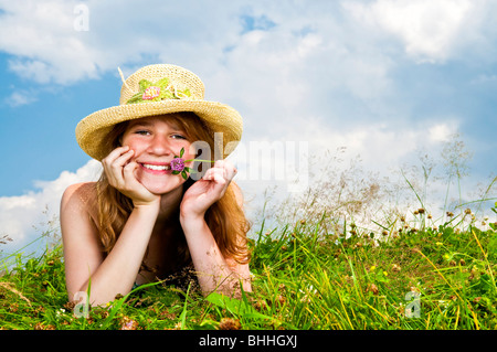 Young teenage girl laying in summer meadow resting chin on hand holding flower - Stock Photo