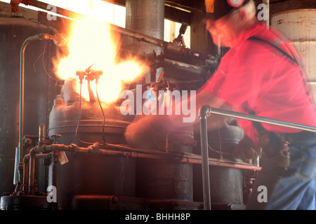 Lighting the glow plug burner on a semi-diesel oil engine - Stock Photo