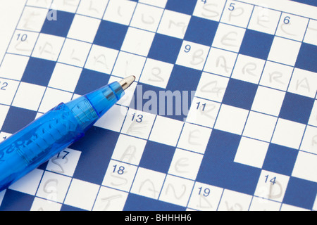 Studio still life UK Europe. Close-up of an incomplete blue and white paper crossword puzzle with a blue ballpoint - Stock Photo