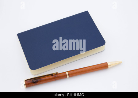 Close-up of a blue moleskine notebook with a wooden ballpoint pen isolated on a white background. - Stock Photo