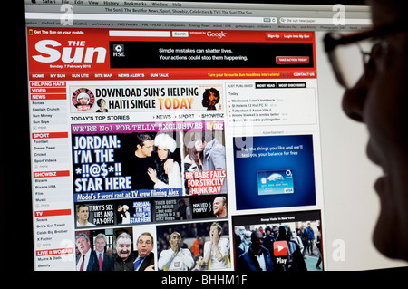 Woman reading The Sun newspaper online edition - Stock Photo