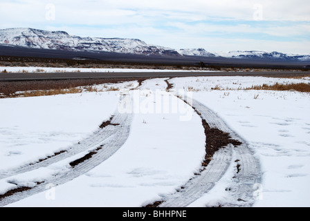 tire marks leaving snow on side of two lane highway in nevada - Stock Photo