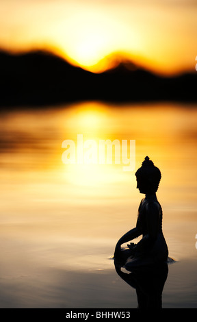 Silhouette of Buddha statue floating on calm still water surface at sunrise in India - Stock Photo