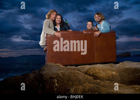 group on couch outside night fun - Stock Photo