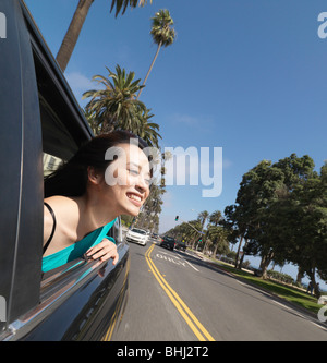 Young woman leaning out of car window - Stock Photo