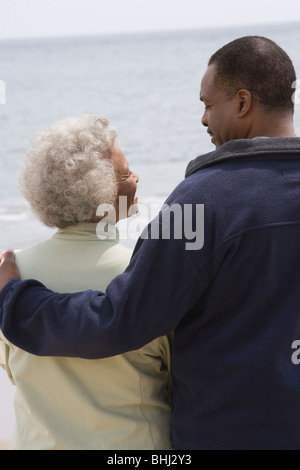Man stands with his arm round a woman at waters edge - Stock Photo
