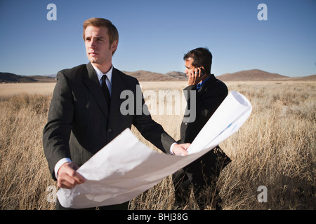 2 men with plans in field, one on phone - Stock Photo