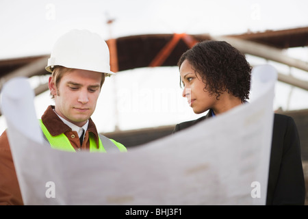 Concerned man and woman with blueprints - Stock Photo