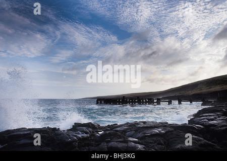 Waves crashing on rocky shoreline - Stock Photo