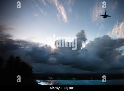 Airplane takes off over dark beach - Stock Photo