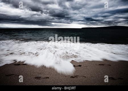 Waves crashing on beach with footprints - Stock Photo