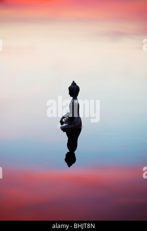 Silhouette of Buddha statue floating on calm still water surface just before sunrise in India - Stock Photo