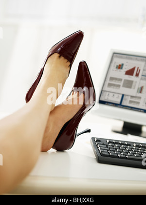 business woman taking off shoes in office. - Stock Photo