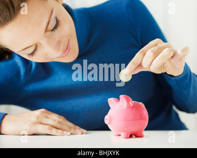 woman putting 1 euro in small piggy bank. Selective focus, Copy space - Stock Photo