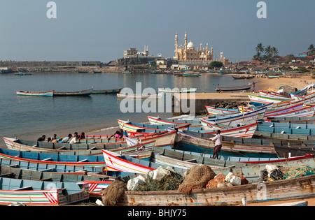 India, Kerala, Kovalam, Vizhinjam village colourful fishing boats on beach - Stock Photo