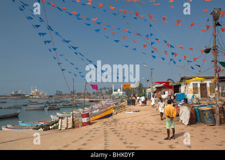 India, Kerala, Kovalam, Vizhinjam village seafront, colourful bunting flags outside old fisherman's church - Stock Photo