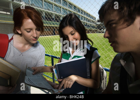 Teenage girls looking at newspaper together, boy standing nearby watching - Stock Photo