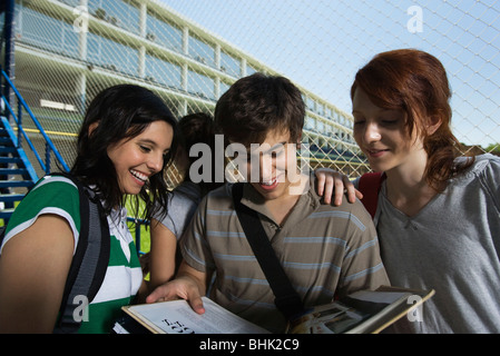 Teenage boy showing girl friends book - Stock Photo