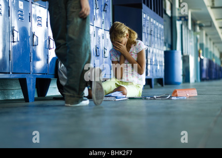 Female junior high student sitting on floor holding head in hands, boy standing smugly nearby - Stock Photo