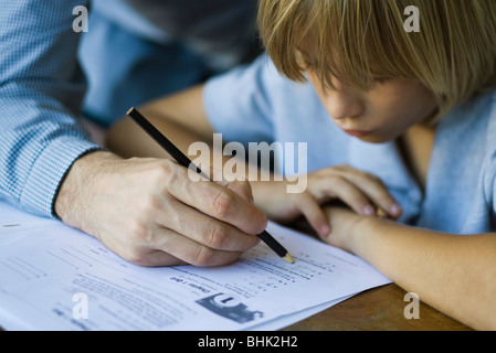 Male junior high student watches as teacher corrects assignment, close-up - Stock Photo