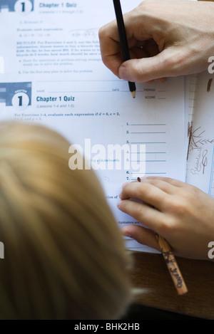 Student watching as teacher grades quiz, close-up - Stock Photo
