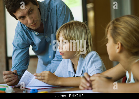 Teacher assisting students with their classwork assignments - Stock Photo