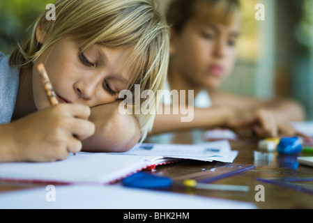Junior high student resting head on arm while writing assignment - Stock Photo