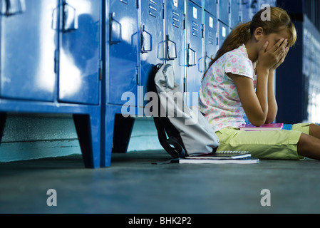 Female junior high student sitting on hall floor near lockers, upset and covering face with hands - Stock Photo