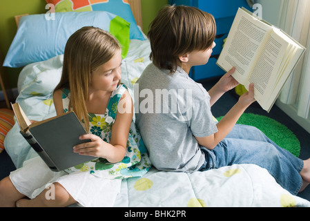 Siblings reading together, girl glancing over shoulder at brother's book - Stock Photo