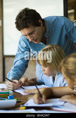 Teacher helping young students with classwork - Stock Photo