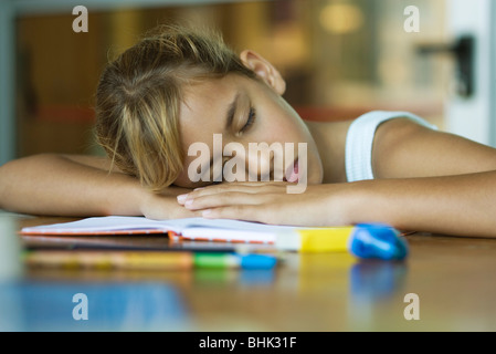 Preteen girl napping, resting head on arms laid across open book - Stock Photo
