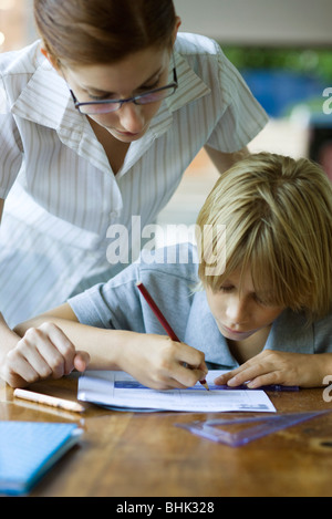 Teacher looking over student's shoulder reviewing their classwork - Stock Photo