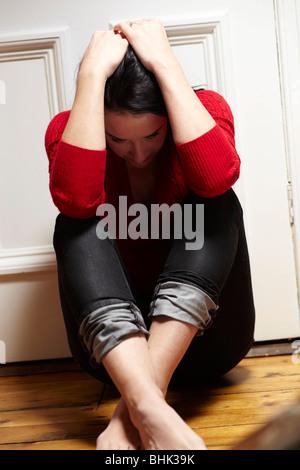 Stressed woman sat on floor - Stock Photo
