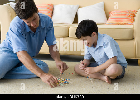 Father and son playing pick up sticks - Stock Photo