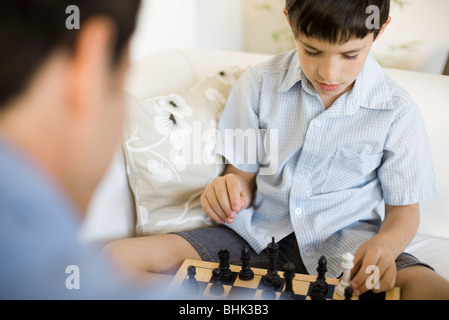 Boy playing chess with his father, cropped - Stock Photo