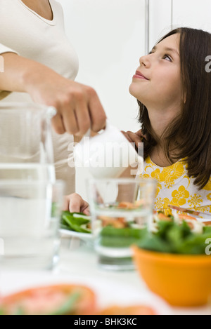 Girl sitting at table looking up at mother serving food Stock Photo