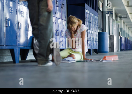 Junior high student sitting on floor crying, boy standing by watching - Stock Photo