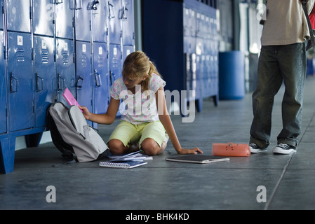 Junior high student picking up dropped school supplies, boy standing by watching - Stock Photo