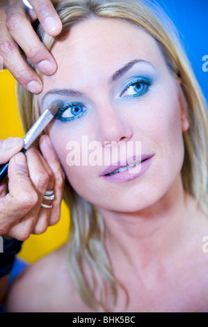 Makeup artist applying eyeshadow on a young woman with eyes open - Stock Photo