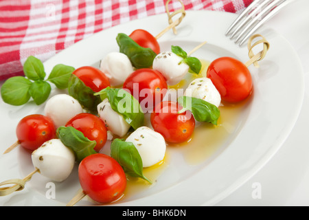 tomato and mozzarella sticks with basil leaves and olive oil on plate, tilted view